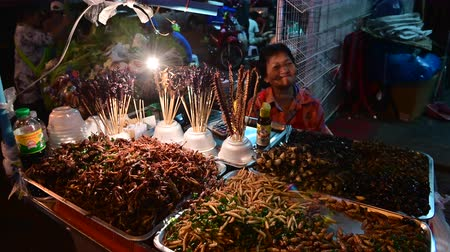 Bangkok, Thailand - December 11, 2019 : Unidentified woman sells bugs in night market at Bangkok Chinatown