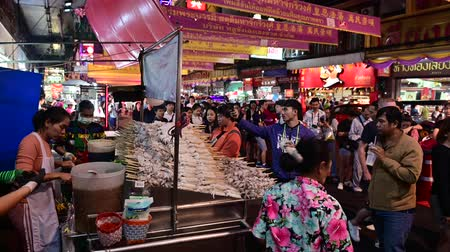 market vendor : Bangkok, Thailand - December 11, 2019 : Thai street food stall with skewers of grilled squid at China town, Bangkok