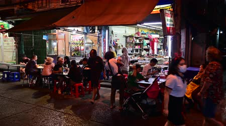 market vendor : Bangkok, Thailand - December 11, 2019 : Unidentified tourists dining street food with traffic is on the road at Chinatown, Bangkok
