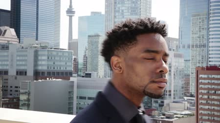 czarne : Afro-american man on a rooftop looking at a big city Wideo