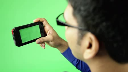 ekran : holding a cell phone isolated on green screen