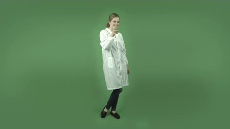 кавказский : attractive caucasian girl wearing a lab coat isolated on chroma green background