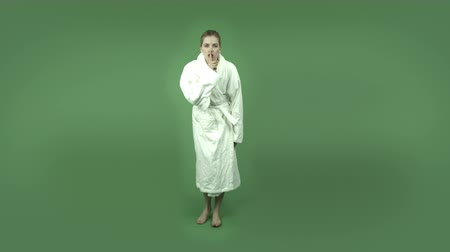 тайна : attractive caucasian girl wearing a bathrobe  isolated on chroma green background