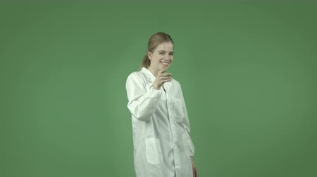 welcome sign : attractive caucasian girl wearing a lab coat isolated on chroma green background
