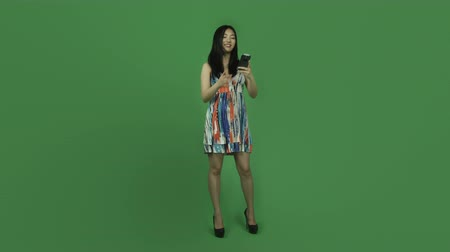 по телефону : Attractive asian girl in her 20s isolated on a greenscreen chroma green background Стоковые видеозаписи