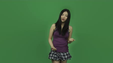 emocje : Attractive asian girl in her 20s isolated on a greenscreen chroma green background Wideo