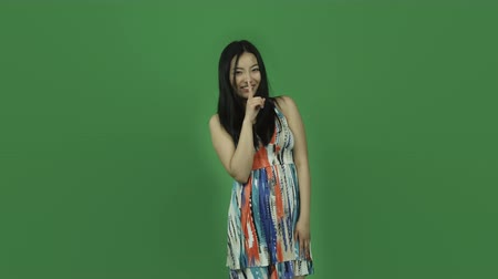 тайна : Attractive asian girl in her 20s isolated on a greenscreen chroma green background Стоковые видеозаписи