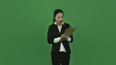 öfke : Attractive asian girl in her 20s isolated on a greenscreen chroma green background Stok Video