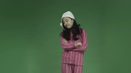 vyčerpaný : young asian adult woman in pajamas isolated on green-screen background