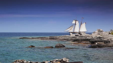 greater : Wide shot of a sailboat moving in a bay, Georgian Bay, Tobermory, Ontario, Canada Stock Footage