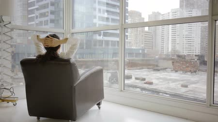 Asian business woman in chair working looking at windows toronto canada city