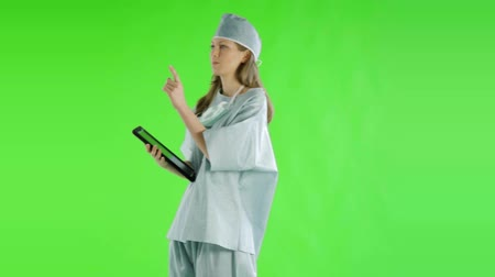 touchpad : caucasian woman greenscreen cut out doctor healthcare nurse scrubs tablet Stock Footage