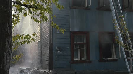 сжигание : Firefighters extinguish the fire. Burning old abandoned house. Slow Motion Video Стоковые видеозаписи