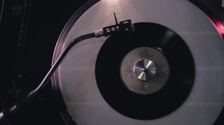 mixer : DJ plays vinyl turntables. In a nightclub - bar. The vinyl record is spinning. Stock Footage