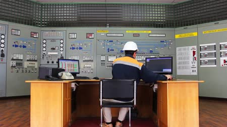 sitting room : engineer works at table in front of panel process control Stock Footage