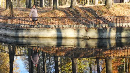 brune : nice woman goes along shore of lake in beautiful autumn city park