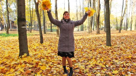 brune : nice woman rotates and scatters yellow leaves in beautiful autumn city park