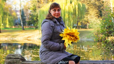 brune : nice woman sits on bench and holds in her hands yellow leaves at beautiful autumn city park near lake