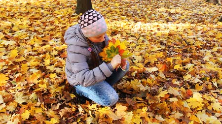 outside : nice teen girl sits squatted and holds yellow leaves in beautiful autumn city park