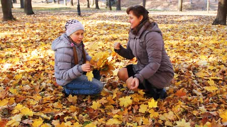 brune : mother with her daughter sit squatted and scatter yellow leaves in beautiful autumn city park Stock Footage