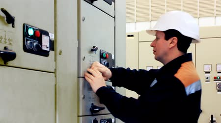 technikus : engineer comes, unlocks and activates electrical equipment from control panel, closeup
