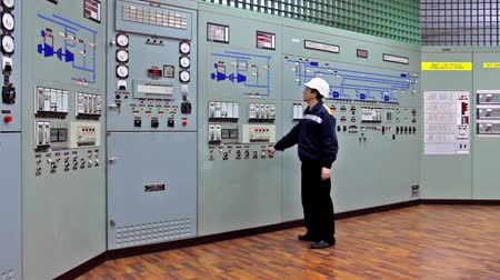 управление : triggered audio-visual emergency warning alarms on main control panel of compressor station, engineer comes and disables it, wide viewing