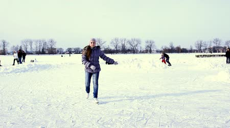 patim : teenage girl skating by winter frozen lake to camera