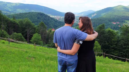 brune : loving couple stands embracing on top of mountain and looks at beautiful view