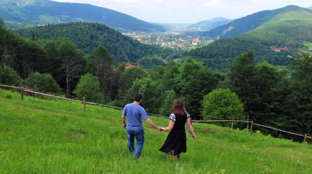 brune : loving couple holding hands going down to beautiful mountains