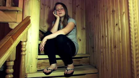 brune : cute teen girl listen cell phone sitting on wooden stairs in home, then she turns off it Stock Footage
