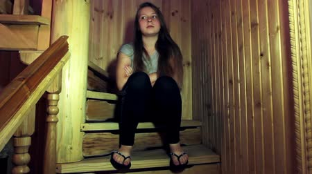 unott : sad teen girl sits and looks around on wooden stairs in home Stock mozgókép