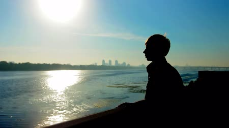 brune : young guy near wide river and far away city, silhouette against sunrise