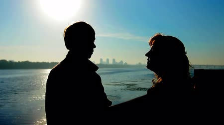 brune : young guy with his mother talking near wide river and far away city, silhouette against sunrise Stock Footage
