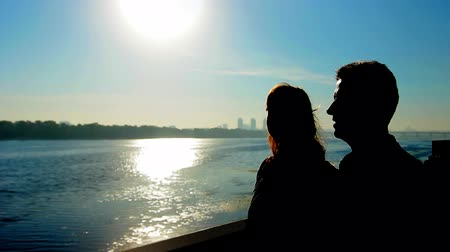 brune : silhouette of couple near wide river against sunrise, far away city Stock Footage