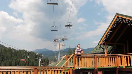 onto : pretty woman stands on porch near resort house and look onto mountain lift in Carpathian Mountains, panorama to sky