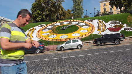órák : man goes and looks at hour on real flower clock in center of Kiev