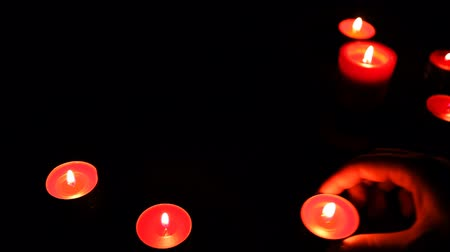 sentiment : female hands put red candles with lights in semicircle on table, dark
