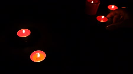 sentiment : female hands put red candles with fusil wax in semicircle, small lights