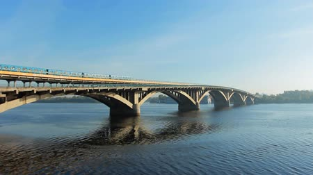 múló : metro train on bridge slowly ride over Dnipro river at sunny day