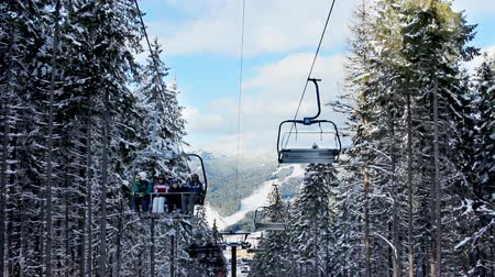 chair lift : skiers going up on hoist through dark forest above snow winter mountains, closeup