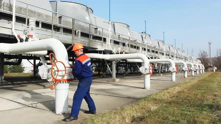 устанавливать : worker opens valve on installation for cooling gas at compressor station of main pipeline