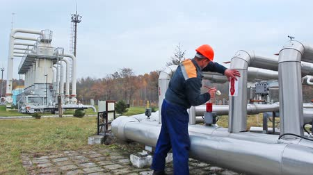válvula : worker draws red arrows on pipes at compressor station of main gas pipeline, timelapse