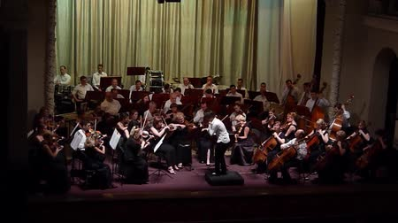 hangjegykulcs : DNIPRO, UKRAINE - JULY 1, 2016: Members of the Symphonic Orchestra - main conductor Natalia Ponomarchuk perform at the Potemkin Palace. Stock mozgókép