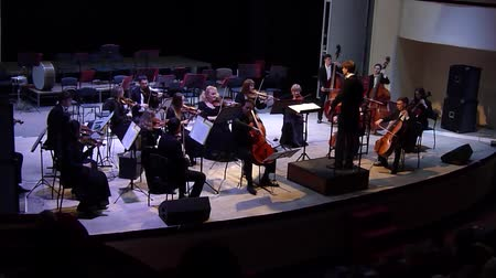 dyrygent : DNIPRO, UKRAINE - JANUARY 14, 2018: Cellist Artem Poludeny and Academic Symphony Orchestra - main conductor Ivan Cherednichenko perform Concert by Carl Philippe Emanuel Bach for cello with orchestra in a minor at the Philharmonic.