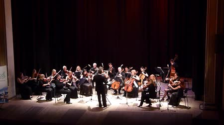 dyrygent : DNIPRO, UKRAINE - JUNE 18, 2018: FOUR SEASONS Chamber Orchestra - main conductor Dmitry Logvin perform Melody by Astor Piazzolla at the State Drama Theater.