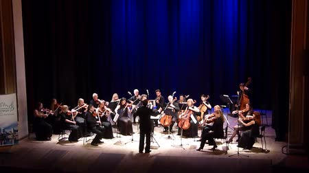 hangjegykulcs : DNIPRO, UKRAINE - JUNE 18, 2018: FOUR SEASONS Chamber Orchestra - main conductor Dmitry Logvin perform Serenade by Edward Elgar at the State Drama Theater. Stock mozgókép