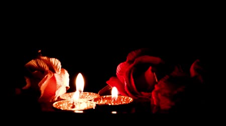 vegetativo : flame of wax candles and floating buds roses on the surface of water Stock Footage