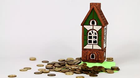 inflação : Decorative house and metal gold coins fall on the plane of the earth
