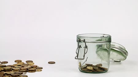 donate : Falling metallic gold coins into a glass jar as an element of saving finances