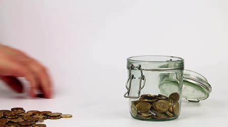 doação : Falling metallic gold coins into a glass jar as an element of saving finances
